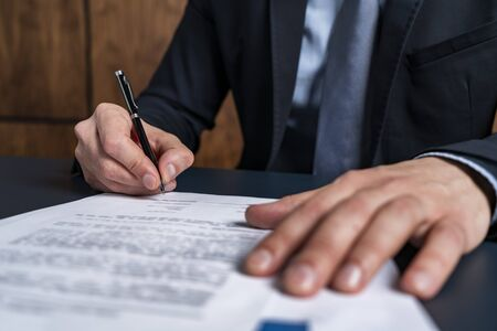 A man broker signing the mortgage contract at the real property agent office. The concept of entering into legal power to take liabilities.