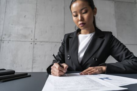 Concentrated young Asian businesswoman signing contract in loft office. Concept of management and paperwork Banque d'images