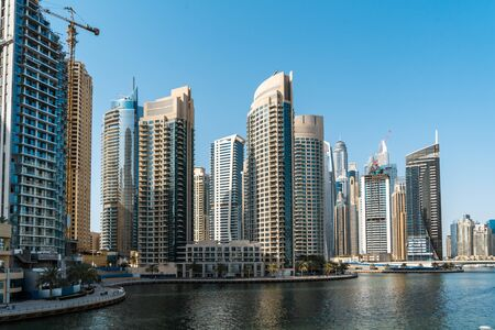 Panoramic view of Dubai skyscrapers in UAE. Dubai Marina prestigious residential area of Dubai close to the sea. Concept of financial success and luxury lifestyle.