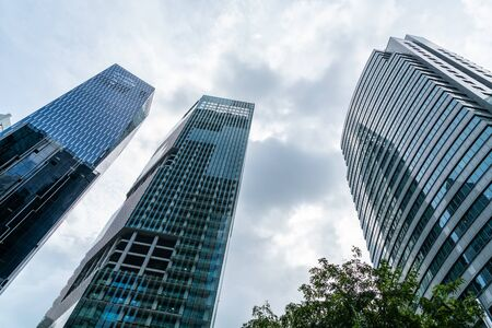 Low-angle view of picturesque skyscrapers of Singapore city downtown at day time. Financial district and trading center hub in Asia region. Concept of success. Modern buildings in high-tech world. Фото со стока