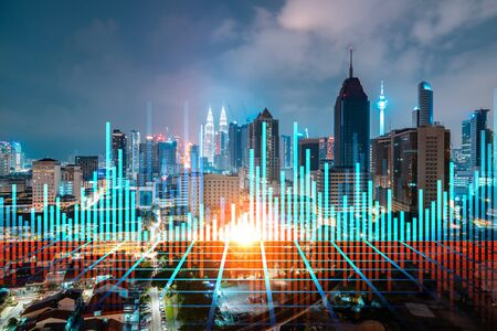 FOREX graph hologram, aerial night panoramic cityscape of Kuala Lumpur. KL is the developed location for stock market researchers in Malaysia, Asia. The concept of fundamental analysis. Reklamní fotografie