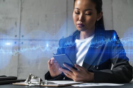 Businesswoman typing phone, work in modern office on new project. forex graph hologram. Double exposure. Concept of success in online trading. Mobile app.