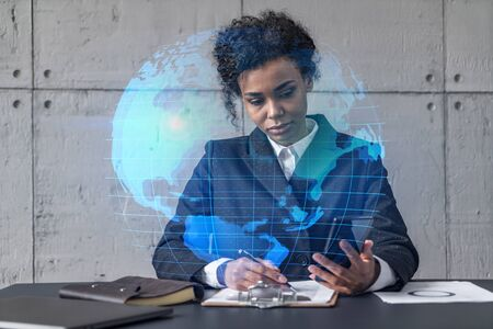 Businesswoman taking notes and world map hologram. Double exposure. Technology security network solution planet earth international business concept. Imagens