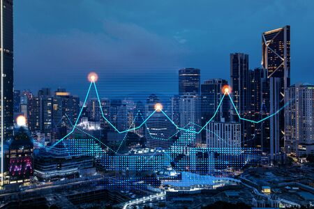 Stock market graph hologram, night panorama city view of Kuala Lumpur. KL is popular location to gain financial education in Malaysia, Asia. The concept of international research. Double exposure.