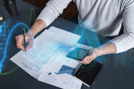 Multi exposure of man signing contract with phone and financial chart hologram. Concept of market analysis, accountant, investment.
