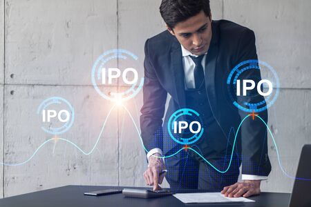 Businessman signs contract and ipo hologram. Double exposure. Formal wear. Concept of market analysis.