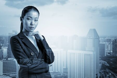 Attractive young Asian business woman in suit with hand on chin thinking how to succeed, new career opportunities, MBA. Singapore on background. Double exposure. Foto de archivo