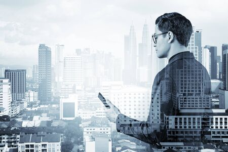 Young handsome businessman in suit and glasses using phone and thinking how to tackle the problem, new career opportunities, MBA. Kuala Lumpur on background. Double exposure.