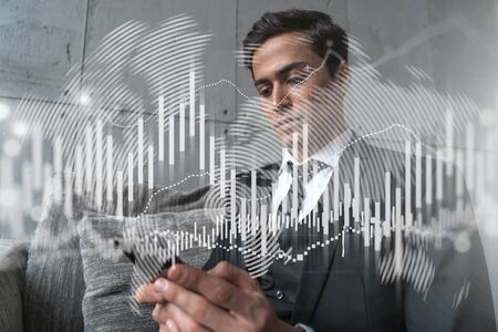 Trader in office working with Smartphone, FOREX graph hologram to analyze market behavior, typing phone. Double exposure. Stock Photo