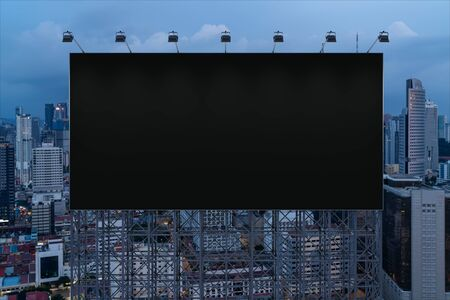 Blank black road billboard with Kuala Lumpur cityscape background at night time. Street advertising poster, mock up, 3D rendering. Front view. Concept of marketing to promote or sell idea or product. Reklamní fotografie