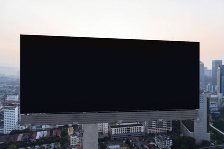 Blank black road billboard with Kuala Lumpur cityscape background at sunset. Street advertising poster, mock up, 3D rendering. Front view. The concept of marketing communication.