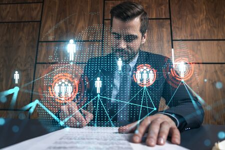 Businessman in office signs contract and social media hologram. Double exposure. Formal wear. Concept of people smm data.