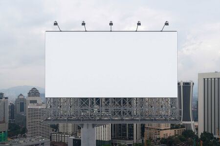 Blank white road billboard with KL cityscape background at day time. Street advertising poster, mock up, 3D rendering. Front view. The concept of marketing communication to promote or sell idea.