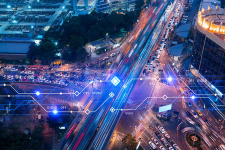 Technology hologram on aerial view of road, busy urban traffic highway at night. Junction network of transportation infrastructure. The concept of developing high-tech science in logistics. 스톡 콘텐츠