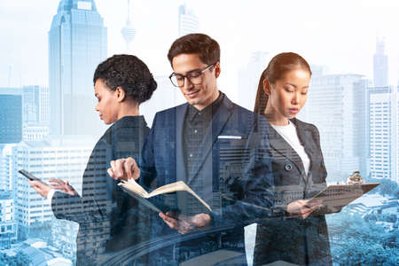 Group of three business colleagues in suits working on project together to gain new career opportunities. Concept of multinational corporate team. Kuala Lumpur. Double exposure. Imagens