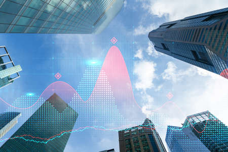 FOREX and stock market chart hologram on low, wide angle view of glass and steel contemporary skyscrapers in financial downtown. The concept of international trading. Double exposure. Stock Photo