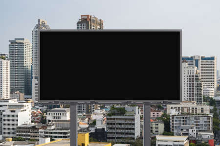 Blank black road billboard with Bangkok cityscape background at day time. Street advertising poster, mock up, 3D rendering. Front view. The concept of marketing communication to promote or sell idea.