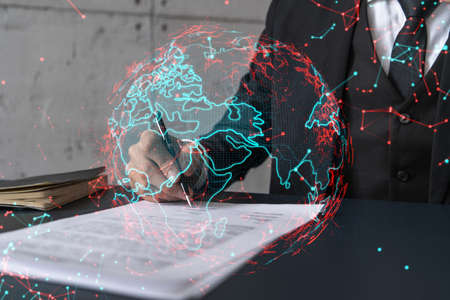 Businessman in suit signs contract. Double exposure with world map hologram. Man signing agreement international business concept. Stock Photo