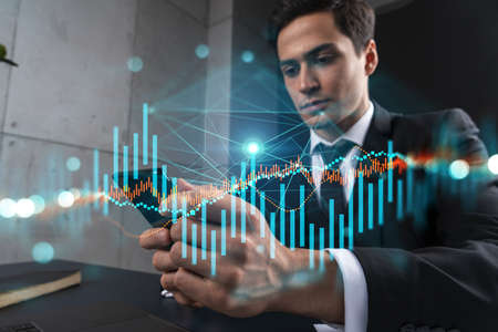 Trader in office working with Smartphone, FOREX graph hologram to analyze market behavior, typing phone. Double exposure. 免版税图像