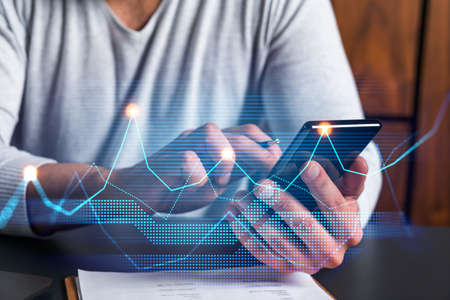 Man using phone. Hands typing smartphone. Double exposure with chart hologram. Close up. Financial graph and analysis concept. On-line research and investment. Stock Photo