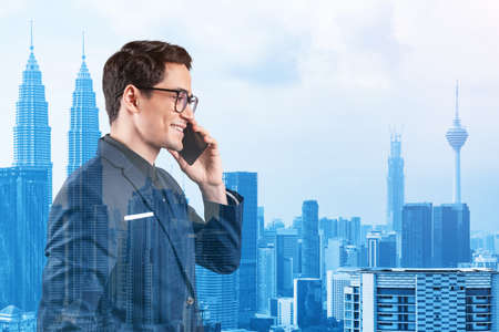 Prosperous handsome entrepreneur in suit and glasses pensively talking phone and looking on Kuala Lumpur cityscape. The concept of problem solving consulting . KL skyscrapers. Double exposure. 免版税图像