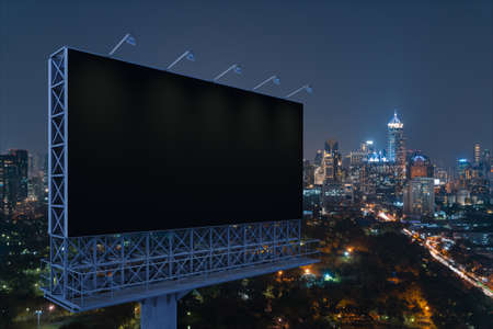 Blank black road billboard with Bangkok cityscape background at night time. Street advertising poster, mock up, 3D rendering. Side view. The concept of marketing communication to promote idea.
