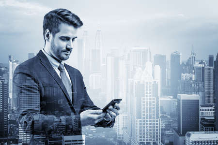 Prosperous European businessman in suit texting phone the details of corporate meeting. Kuala Lumpur cityscape. The concept of business communication. KL skyscrapers. Double exposure.