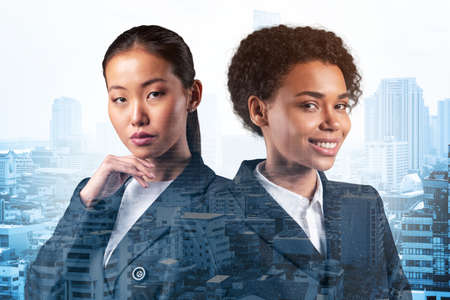 Two young attractive businesswoman in suits dreaming about new career opportunities after MBA graduation. Concept of multinational corporate team Bangkok on background. Double exposure.