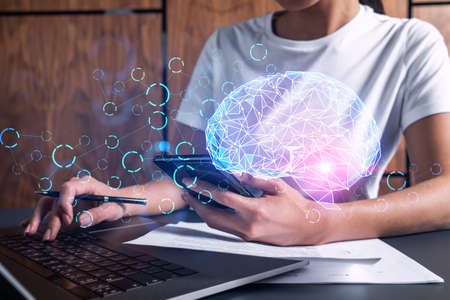 Businesswoman typing on laptop in office. Brain network illustration hologram.