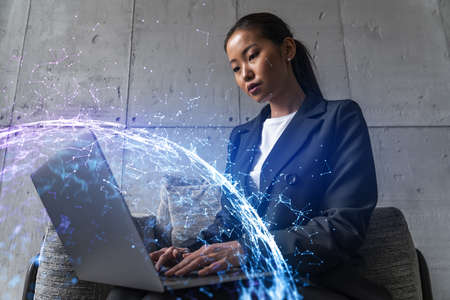 Businesswoman typing on laptop work in modern office on new project. Abstract tech icon drawing hologram. Double exposure. Concept of success. 免版税图像