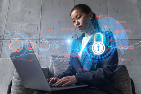 Businesswoman typing on laptop work in modern office on new project. Lock icon drawing hologram. Double exposure. Concept of success. 免版税图像
