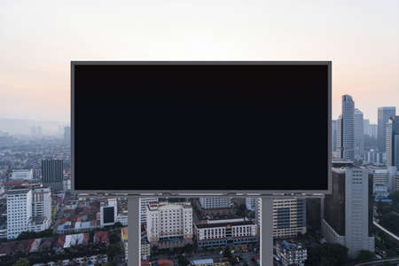 Blank black road billboard with Kuala Lumpur cityscape background at sunset. Street advertising poster, mock up, 3D rendering. Front view.