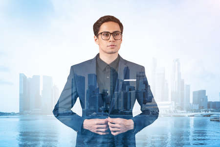 Young handsome businessman in suit and glasses dreaming about new career opportunities after MBA graduation. Singapore on background. Double exposure. Archivio Fotografico