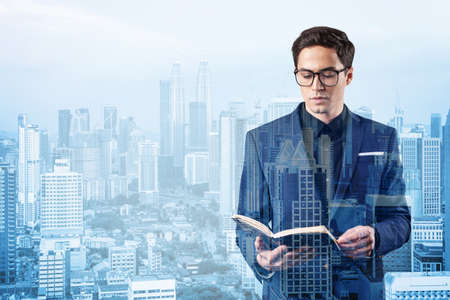 Young handsome businessman in suit and glasses thinking how to tackle the problem, new career opportunities, MBA assignment. Kuala Lumpur on background. Double exposure. Zdjęcie Seryjne