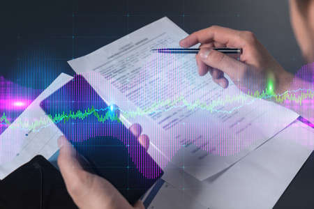 Multi exposure of man signing contract with phone and forex chart hologram. Concept of financial market, stock exchange, investment in bonds.