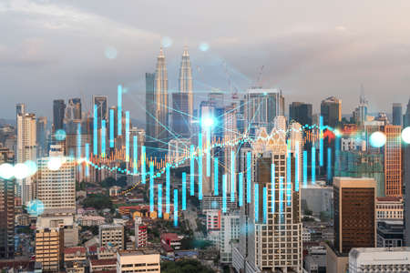 Glowing FOREX graph hologram, aerial panoramic cityscape of Kuala Lumpur at sunset. Stock and bond trading in KL, Malaysia, Asia. The concept of fund management. Double exposure. 스톡 콘텐츠