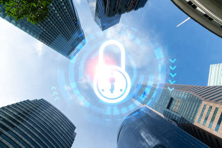 Padlock icon hologram on low, wide angle view of glass and steel contemporary skyscrapers in financial downtown. The concept of success in cyber security intelligence. Multi exposure.