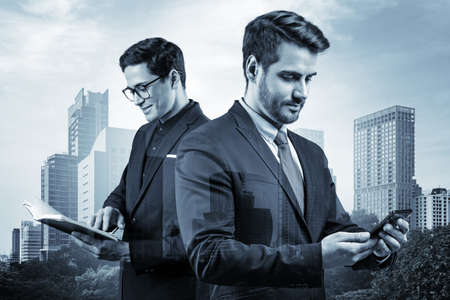 Two young handsome businessmen in suits working on project together to gain new career opportunities. MBA education. Teamwork concept. Bangkok on background. Double exposure.