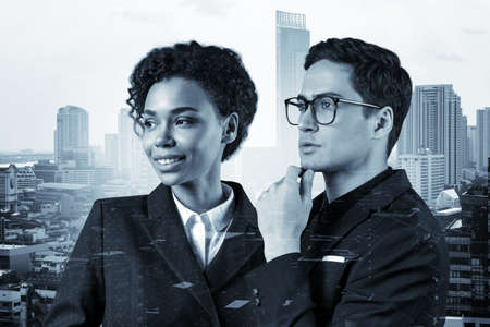 Portraits of two young business partners in suits dreaming about new career opportunities. Multinational teamwork concept. Bangkok on background. Double exposure. Foto de archivo