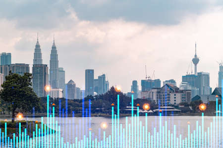 Market behavior graph hologram, sunset panoramic city view of Kuala Lumpur. KL is popular location to achieve financial degree in Malaysia, Asia. The concept of financial data analysis.