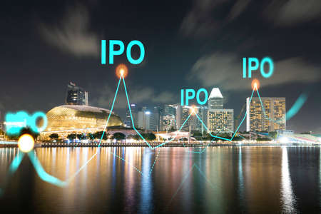 Initial public offering hologram, night panoramic city view of Singapore. The financial center for multinational corporations in Asia. The concept of boosting the growth by IPO process. Stock Photo