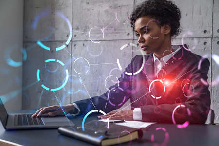 Businesswoman typing on laptop work in modern office on new project. Abstract tech icon drawing hologram. Double exposure. Concept of success.