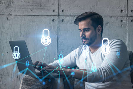 A serious caucasian programmer in casual wears, using laptop to develop a new security system to protect data. Double exposure. IT lock hologram icon.