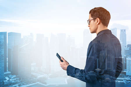 Young handsome businessman in suit and glasses using phone and thinking how to tackle the problem