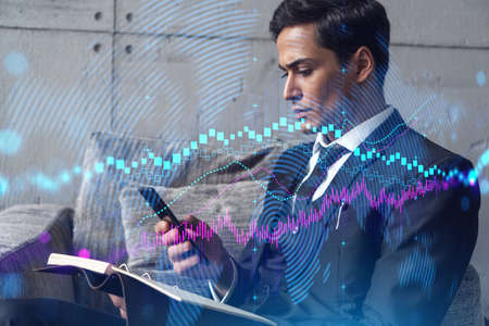 A businessman in office taking notes using phone and stock graph hologram. Multiexposure. Formal wear.