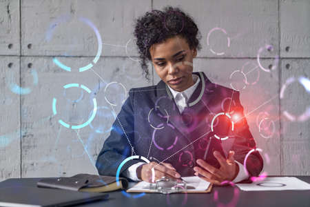 Businesswoman taking notes and abstract tech icons hologram. Double exposure. Technology security network solution concept.