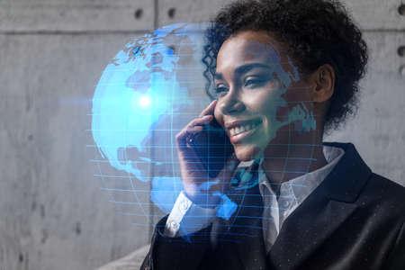 Businesswoman speaks phone and world map hologram. Double exposure. Foto de archivo