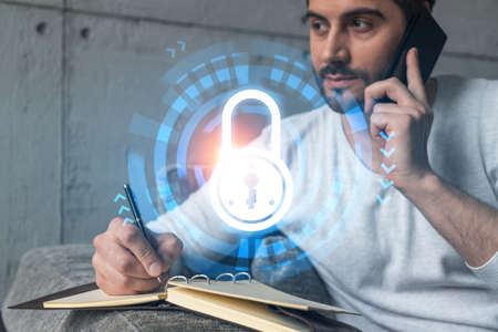 Handsome manager in casual, speaking phone and taking notes at office try to determine IT needs of customer to protect they information. Double exposure. The concept of confidentiality and privacy.