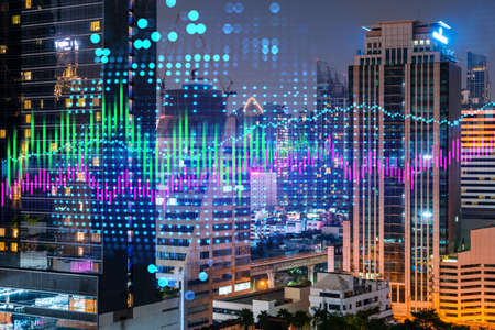 Stock market graph hologram, night panorama city view of Bangkok, popular location to gain financial education in Asia. The concept of international research. Double exposure.
