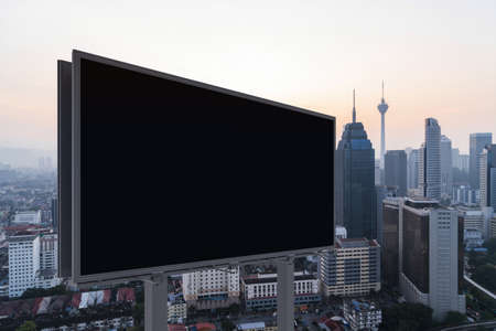 Blank black road billboard with KL cityscape background at sunset. Street advertising poster, mock up, 3D rendering. Side view. The concept of marketing communication to promote or sell idea.